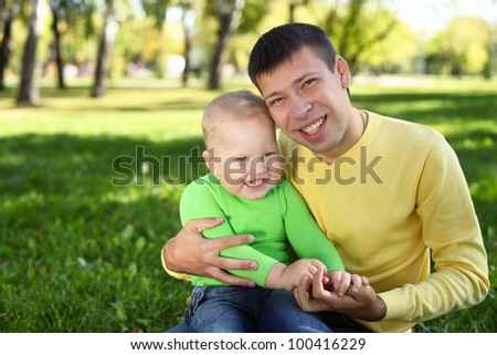 Father with little son in green summer park