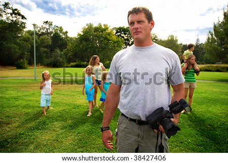 Father with six children preparing to photograph them playing at a park - stock photo