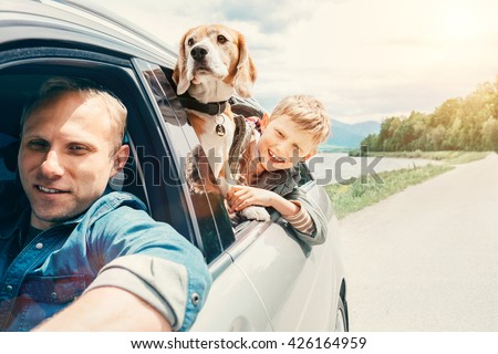 Father with son and dog look from the car window - stock photo