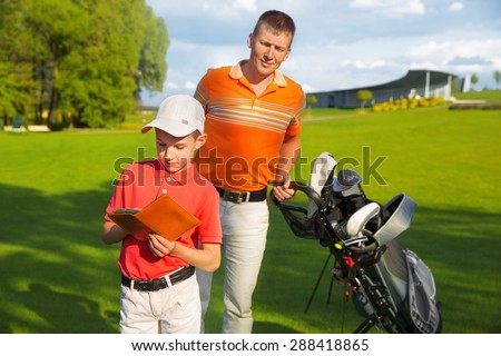 Father with son are counting points of game at golf course  - stock photo