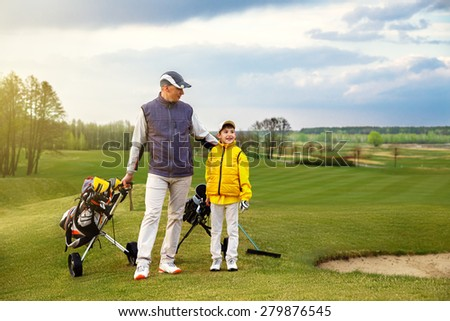Father with son are training at golf course  - stock photo