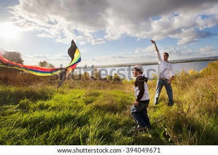 father with son in autumn playing with kite - stock photo