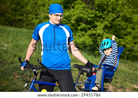 father with son in bicycle chair - stock photo