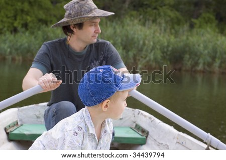 father with son in row boat - summertime - stock photo