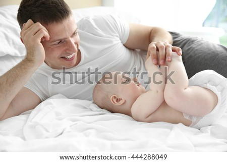 Father with son lying on bed - stock photo