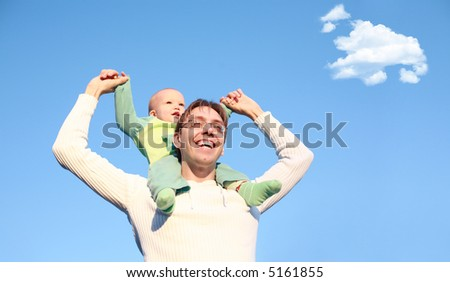 Father with son on shoulders. Focus on father's face - stock photo