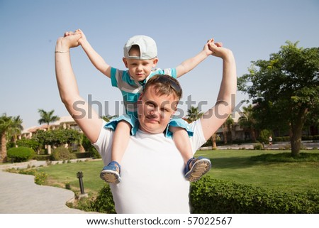father with son on shoulders, sunny day - stock photo
