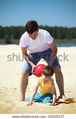 father with son play with ball on sand