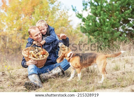 Father with son playing with dog on autumn forest glade - stock photo