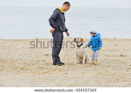 father with son playing with dog on the beach - stock photo