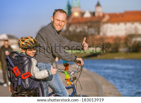 Father with son riding by bicycle along the river waterfront in Krakow - stock photo