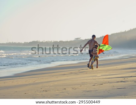 father with son, sunset at the seacoast playing kite, happy family on vacation, silhouette - stock photo