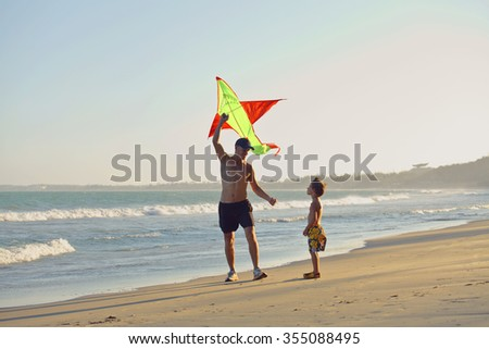 father with son, sunset at the seacoast with kite, happy family on vacation, silhouette - stock photo