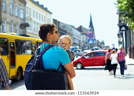 father with son walking through crowded city street