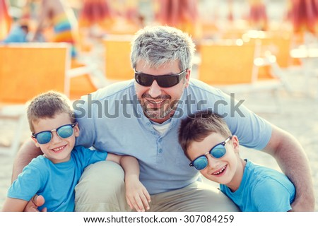 Father with sons on beach, happy family, vintage style - stock photo