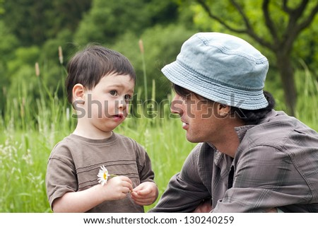 Father with toddler son talking on a green summer meadow. - stock photo