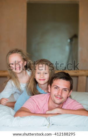 Father with two adorable little girls having fun in bed  - stock photo