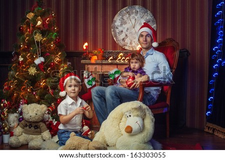 Father with two children near the New Year tree - stock photo