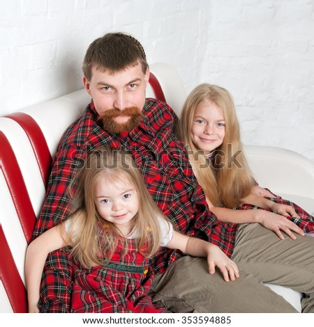 Father with two daughters cuddling together  - stock photo