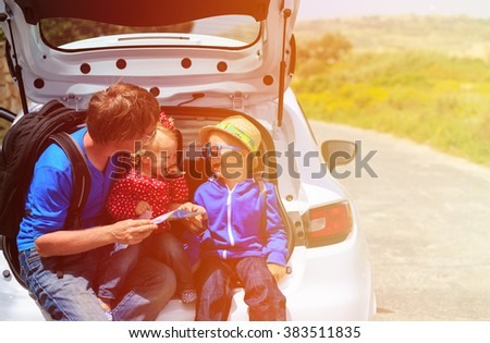 father with two kids looking at map while travel by car - stock photo