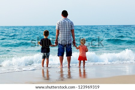 father with two kids on vacation at sea - stock photo