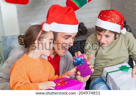 father with two kids open christmas presents, wear santa hat sitting on couch living room - stock photo
