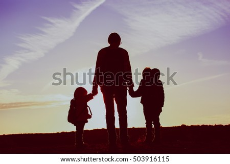father with two kids travel at sunset