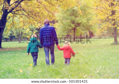 father with two kids walking in autumn fall nature