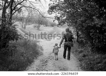 father with young daughter and son walking in forest ( black and white ) - stock photo