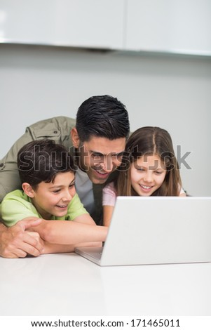 Father with young kids using laptop in the kitchen at home - stock photo