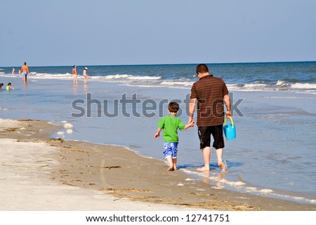 Father with young son walking on the beach in South Carolina. - stock photo