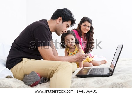 father working on the laptop with mother and daughter in the background, Indian family of three using laptop - stock photo