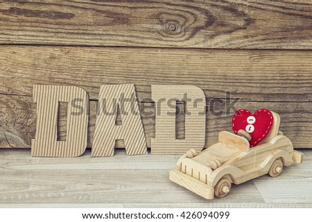 Fathers day background with cardboard letters and wooden toy car. Fathers Day message with wooden toy car and heart. Happy fathers day concept. - stock photo