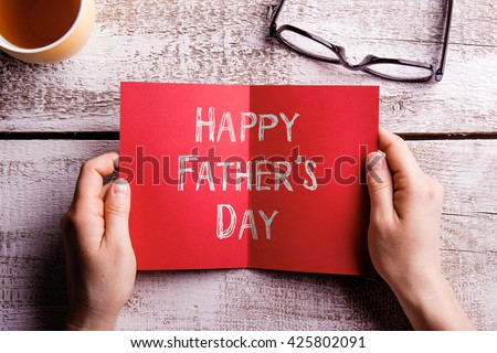 Fathers day composition. Hands of dad holding greeting card. Fathers day. Concept for fathers day celebration. Best father. Child and father concept. Happy fathers day text. - stock photo