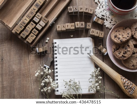 Fathers day concept ,Blank note book and letter spelling the word happy fathers day on wooden stampers with copy space , Natural toned image - stock photo