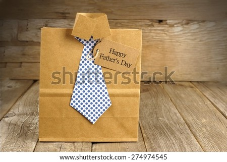 Fathers Day handmade shirt and tie gift bag with greeting card on a wood background - stock photo