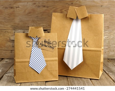 Fathers Day handmade shirt and tie gift bags with greeting card on a wood background - stock photo