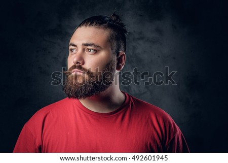 Fatty bearded male in a red t shirt on grey background.