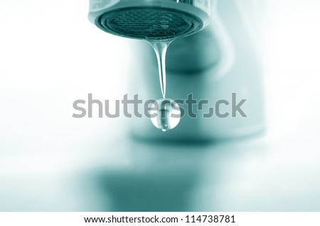 Faucet and falling droplet - stock photo