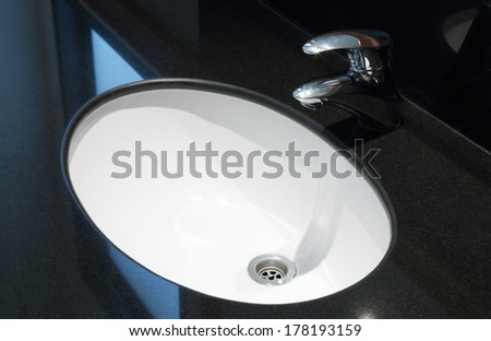 Faucet and white sink in the bathroom with black marble - stock photo