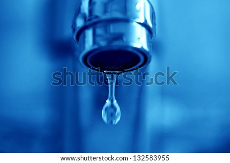 Faucet drip's in blue tone. Small depth of field. - stock photo