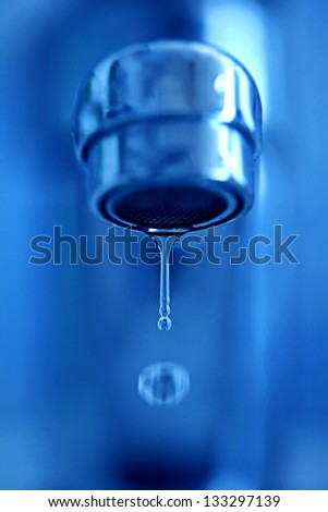 Faucet drip's with water in motion. Small depth of field. - stock photo