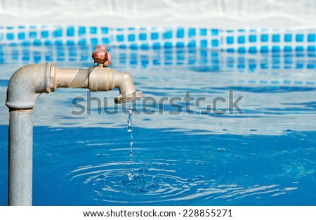 faucet dripping in a blue pool on a sunny day - stock photo