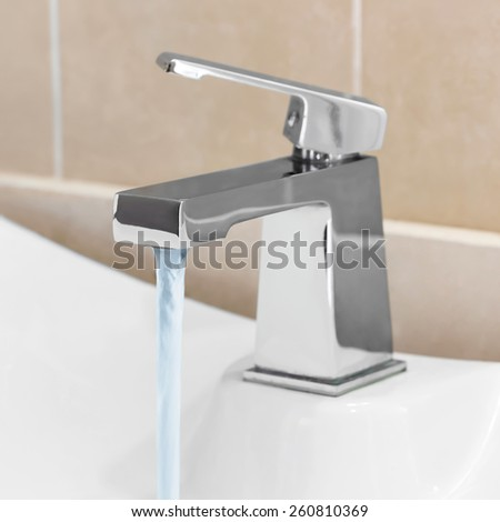 Faucet in bathroom, water is running - stock photo