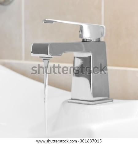 Faucet in bathroom, water is running - stock photo
