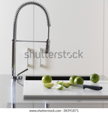 Faucet of the kitchen(cuisine) with lemons - stock photo
