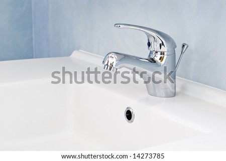 faucet on white sink in bathroom - stock photo