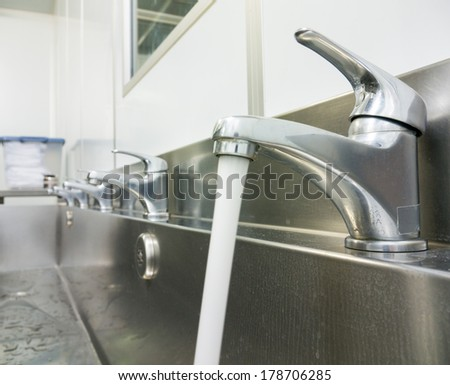 faucet row on the stainless sink - stock photo