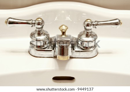 faucet with handles and white sink - stock photo