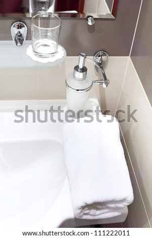 Faucet with soap dispenser in bathroom. - stock photo